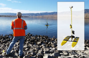 Field crew at edge of water controlling Hydrone in Chatfield Reservoir to collect bathymetry data