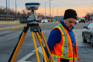 Field crew member in safety vest sets up survey equipment base station on urban street with vehicles in background