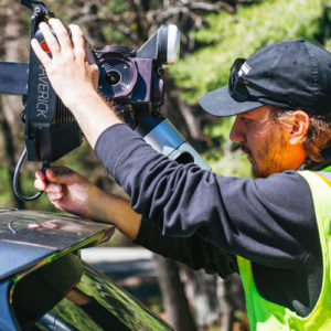 A field crew member in a safety vest installing the Maverick lidar collection technology onto a vehicle