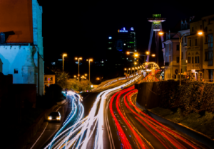 time-lapse of car lights over urban bridge with buildings