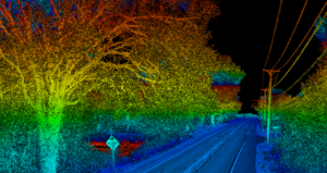 Lidar point cloud showing oblique rural roadway with distribution telephone wires and poles, trees, and traffic sign