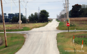 Rural road intersection with utility poles, wind turbines, stop sign, and buried fiber cable signs