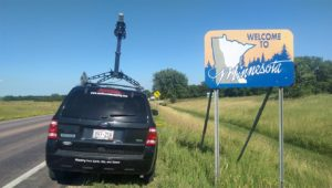 """Continental Mapping vehicle-mounted Maverick next to """"Welcome to Minnesota"""" sign at Minnesota border"""