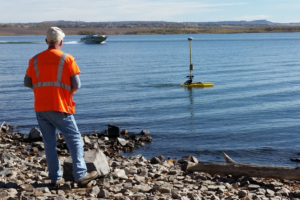 Field crew at edge of waterusing HyDrone to collect bathymetry in the Chatfield Reservoir, Colorado