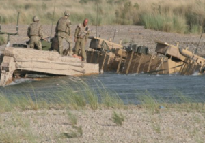 US Soldiers stand on Humvee in the water