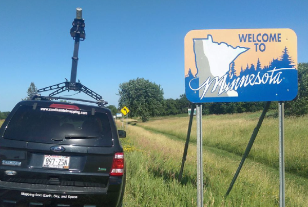 "Continental Mapping vehicle-mounted Maverick next to ""Welcome to Minnesota"" sign at Minnesota border"