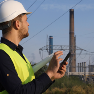 Engineer in safety vest and hard hat using tablet with power plant in background.