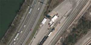 Aerial imagery of highway with vehicles, train tracks, and edge of body of water in Tenneessee