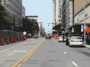 Vehicle POV of urban streets consisting of parked vehicles, construction cones, traffic signs, and stop lights
