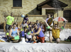 Continental Mapping employees pose in beachwear in the middle of winter outside HQ in Sun Prairie, WI