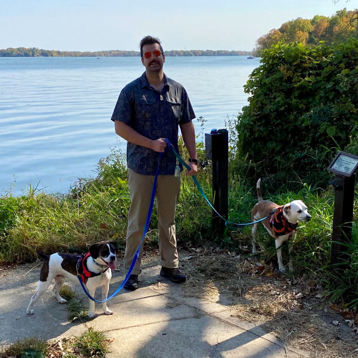 Image of Kyle Nikolay with two dogs on lakeshore