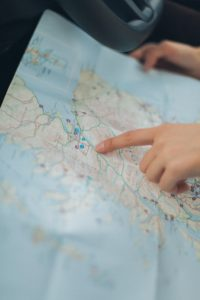 person pointing out location on physical map