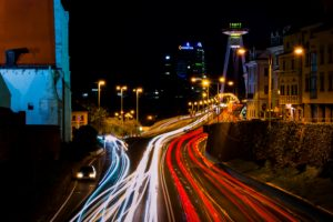 time-lapse of car lights over a urban bridge with buildings