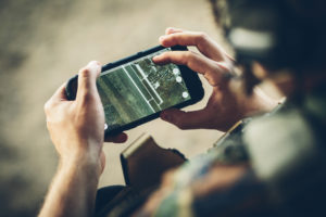 Soldier looking at aerial imagery on mobile phone