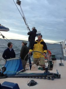CMC employee, Eric Lane, steers a small ship with crewmates over open water.