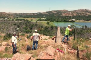 3 survey crew members set up survey equipment on rocky hill with lake and hills in background at Fort Sill, Oklahoma.